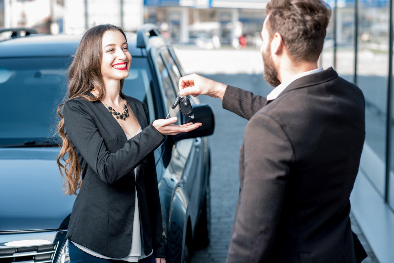 Un homme donnant des clefs de voiture à une femme avec un voiture en arrière plan
