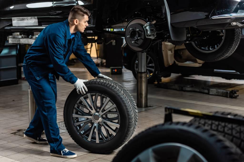 Un garagiste qui tient un pneu