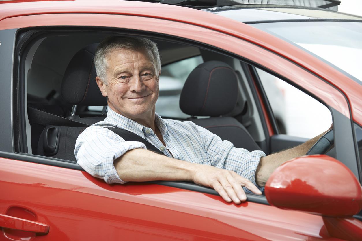 Une personne âgée au volant de sa voiture rouge