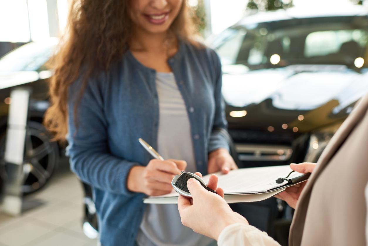 Une femme qui signe un contrat de voiture